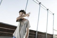 Para fora o menino cansado limpa a boca após a bebida Imagens de Stock