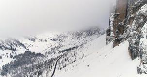 Para a frente aéreo com a floresta nevado da montanha, da estrada e das madeiras na passagem de Sella Tempo nevoento nublado do m filme