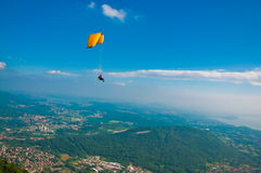 Para-glider. Side view of para-glider in blue sky over forested countryside and towns or villages Stock Photos