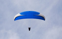 Para glider. Blue and white para glider against a light blue sky with wisps of cloud Royalty Free Stock Photos