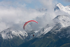 Para-glider againt the alps. A para-glider flies over snow covered mountains in the swiss alps Stock Photo