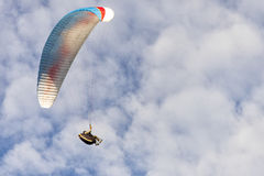 Para glider in fight, hovers in cloudy blue sky. Para glider in fight, hovers in blue sky and cloudy, blue and white style of Para glider stock images