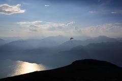 Paragliding over mountains and lake at sunset. Extreme adventure sport. Royalty Free Stock Photos