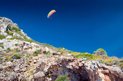 Para glider flying above the rocky hill. In the clear sky Stock Image