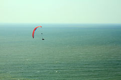 Para glider flying in blue sky over the ocean. Stock Photos