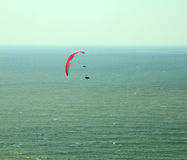 Para glider flying in blue sky over the ocean. Stock Image