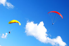 Para-glides. Red and yellow para-glides on blue sky Royalty Free Stock Photos