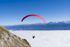 Para gliding in the Austrian Alps over a sea of clouds. Stock Photography