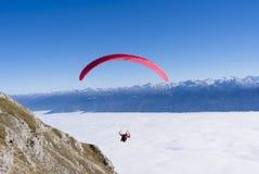 Para glidning i de österrikiska fjällängarna över ett hav av moln Arkivbild