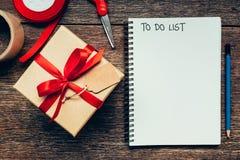 Para hacer la lista en el cuaderno en el fondo de madera de la tabla con el espacio Fotos de archivo libres de regalías