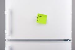 Para hacer la lista en el documento de nota verde sobre el refrigerador blanco Fotografía de archivo libre de regalías