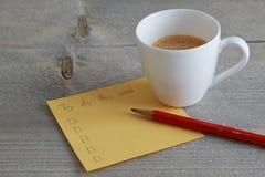 Para hacer la lista en el papel de nota amarillo con el lápiz y el café Imagenes de archivo