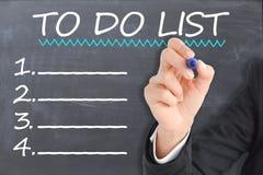 Para hacer la lista hecha por la empresaria en la pizarra, el plan empresarial y las blancos de la compañía por el Año Nuevo imagenes de archivo