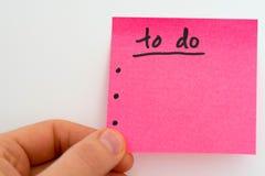 Para hacer la lista por el Año Nuevo en rosa con una mano Fotos de archivo libres de regalías