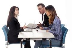 Para i biznesowa kobieta z laptopem siedzimy przy stołem i dyskutujemy obrazy royalty free