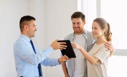 Para i pośrednik handlu nieruchomościami z pastylka komputerem osobistym przy nowym domem Fotografia Stock