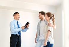 Para i pośrednik handlu nieruchomościami z pastylka komputerem osobistym przy nowym domem Zdjęcie Stock