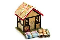 Pequeña casa en un fondo blanco y rollos del dinero Fotos de archivo