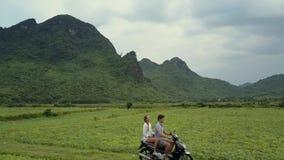 Para jedzie hulajnogę wzdłuż trudnej drogi w pole wierzchu widoku zdjęcie wideo