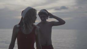 Para jest ubranym Santa kapelusz przy plażą zdjęcie wideo