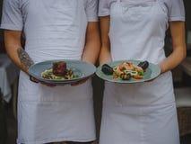Para kelnery trzyma talerze Kelnera i kelnerki porci jedzenie na zamazanym tle Klasyczny restauracyjny pojęcie Fotografia Stock