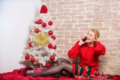 Para la Navidad que espera Saludo del buzón de voz El smartphone alegre del control de la mujer disfruta de la conversación telef fotografía de archivo