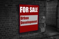 Para la venta con el desarrollo urbano escrito en una muestra atada a una pared Fotos de archivo