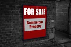 Para la venta con la propiedad comercial escrita en una muestra atada a una pared Fotos de archivo