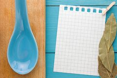 Para las recetas de cocinar de registración y las cocinas Un trozo de papel con un perno en el tablero de madera de la turquesa y Fotografía de archivo libre de regalías