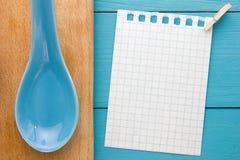 Para las recetas de cocinar de registración y las cocinas Un trozo de papel con un perno en el tablero de madera de la turquesa y Imagenes de archivo