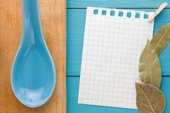 Para las recetas de cocinar de registración y las cocinas Un trozo de papel con un perno en el tablero de madera de la turquesa y Imagen de archivo libre de regalías
