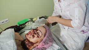 Para lavar apagado el chocolate en la cara del ` s de la muchacha con una esponja terapia del balneario del chocolate almacen de video