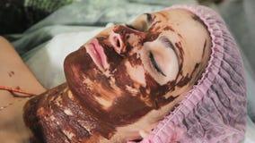Para lavar apagado el chocolate en la cara del ` s de la muchacha con una esponja terapia del balneario del chocolate Cierre para almacen de video