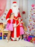 Para los niños en el Año Nuevo Eve Santa Claus vino, ellos lo abraza feliz Fotografía de archivo