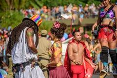 Para mężczyzna z dreadlocks i młoda kobieta na tle rozmyty mężczyzna w czarcim odprowadzeniu na stilts kostiumu i kobiety zdjęcia royalty free