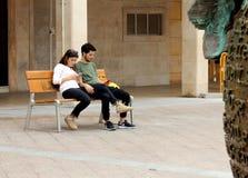 Para młodzi ludzie siedzi na ławce jest oglądająca ich telefon komórkowego sprawdzać i obraz stock