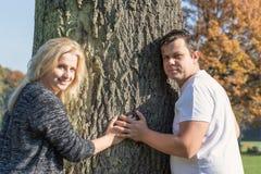 Para młodzi ludzie trzyma ręki na drzewnym bagażniku wpólnie Obrazy Royalty Free
