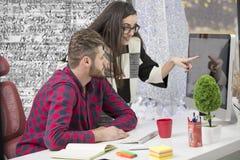 Para młodzi projektanci pracuje przy nowożytnym biurem, dwa coworkers dyskutuje zabawa projekt nad laptopem, zdjęcia royalty free