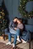 Para małżeńska obejmuje tenderly na kanapie w wieczór w żywym pokoju dekorował z nowego roku drzewem obraz royalty free