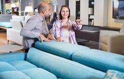 Para małżeńska patrzeje dla nowej eleganckiej kanapy Zdjęcia Stock