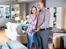 Para małżeńska patrzeje dla nowej eleganckiej kanapy Fotografia Stock