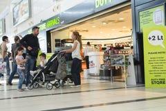 Para małżeńska z dziećmi i pram pozycja w myśli przy wejściem bezcłowy sklep dla przyjazdów Obrazy Stock