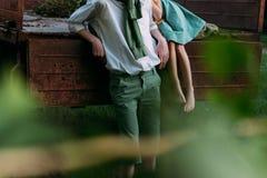 Para mirar de detrás arbustos hojas borrosas al principio de la foto una muchacha descalza en un vestido verde se sienta en el o  Fotos de archivo libres de regalías