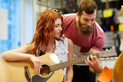 Para muzycy z gitarą przy muzycznym sklepem Obraz Royalty Free