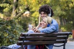 Para na ławce z hełmofonami obrazy royalty free