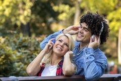 Para na ławce z hełmofonami zdjęcie stock