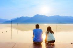 Para na drewnianym porcie przy jeziorem na zmierzchu Zdjęcie Stock
