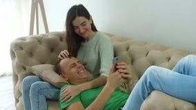Para na kanapie cieszy się środek zawartość w smartphone zdjęcie wideo
