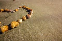 Para o amor da praia, os feriados e o curso, escudos de uma forma do coração na praia foto de stock royalty free