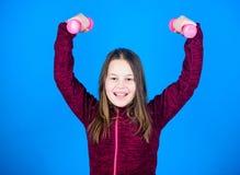 Para o corpo mais forte Conceito da reabilitação menina que exercita com dumbbell Exercícios do peso do novato Posse da criança imagens de stock